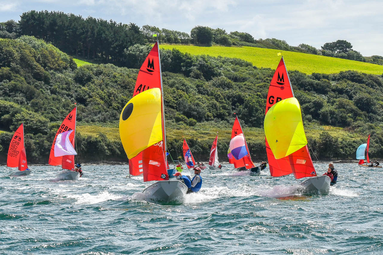 A white Mirror dinghy leading the fleet under spinnakers